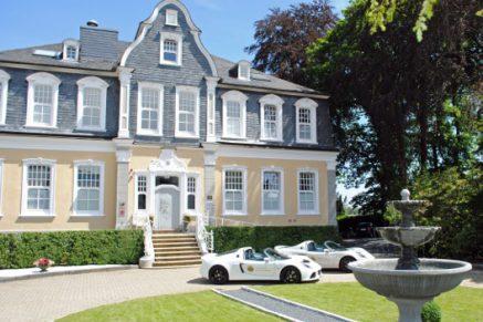 Villa in grau und gelb mit Garten und davor geparkten weißen Lotus Autos.